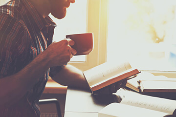 Man drinking coffee and reading a book.