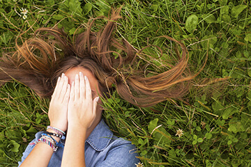 Girl lying in the grass, covering her face.