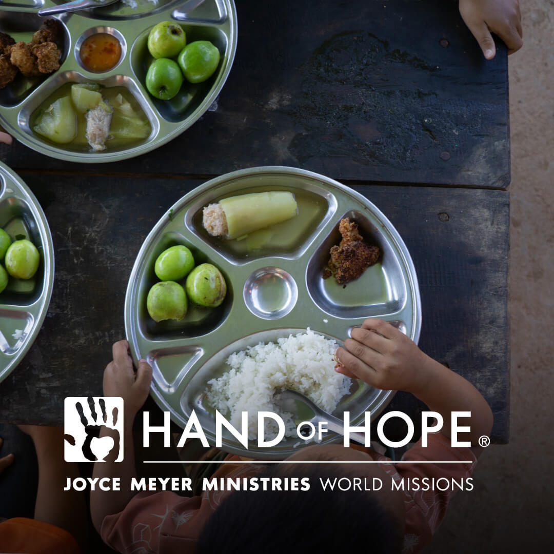 Hand of Hope Logo - Child eating food, sitting at a table.